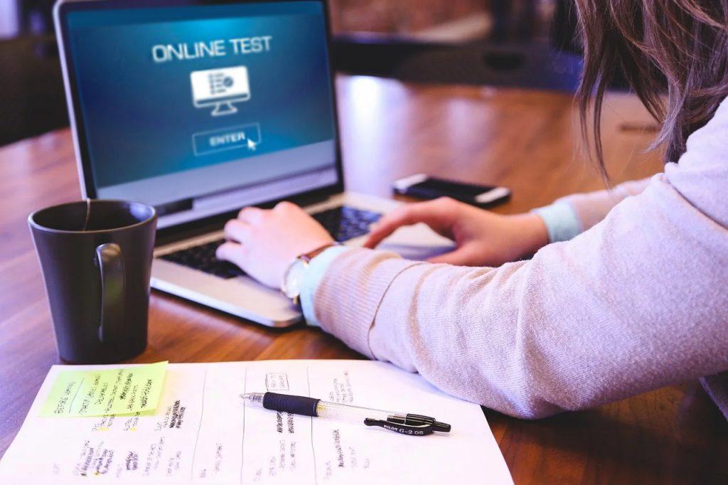 cô gái đang làm bài kiểm tra trực tuyến trên laptop và giấy nháp