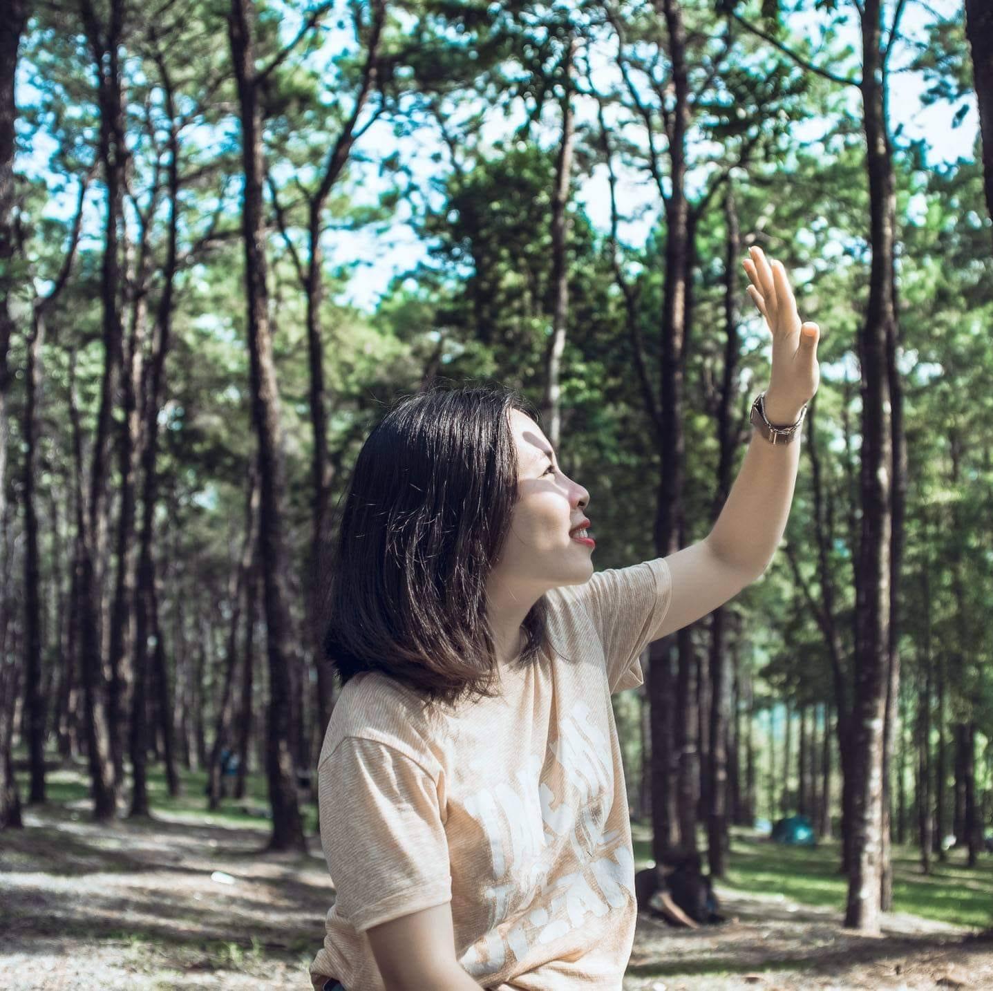 một cô gái đang giơ tay che nắng trong rừng