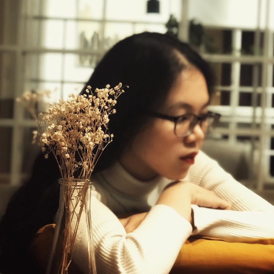 một bình hoa có nền là một cô gái tóc dài đeo kính đang trầm tư